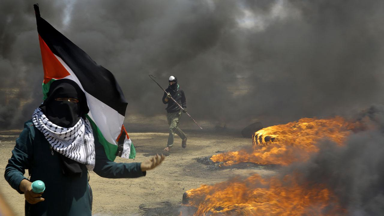 A woman holds a Palestinian flag as a protester burns tires near the Israeli border fence, east of Khan Younis, in the Gaza Strip, Monday, May 14, 2018.