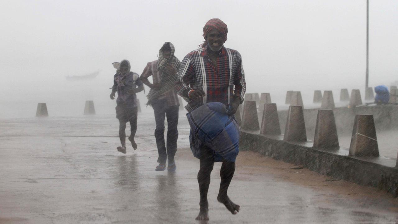 People run for shelter as heavy rain and wind gusts rip through the Bay of Bengal coast at Gopalpur, Orissa, about 178 miles north east of Visakhapatnam, India on Oct. 12, 2014.