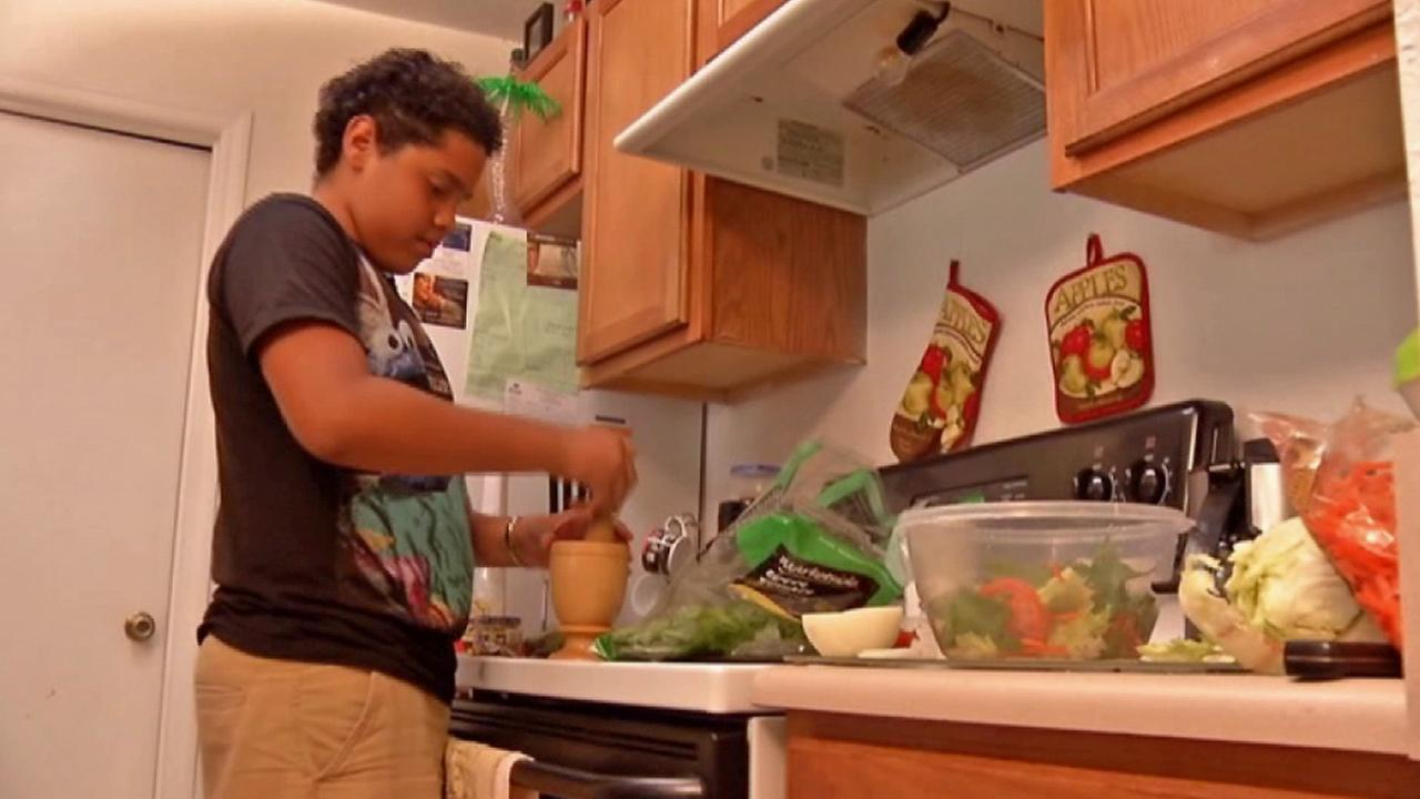 Arturo Vega, 14, prepares a salad in this Oct. 2014 photo.