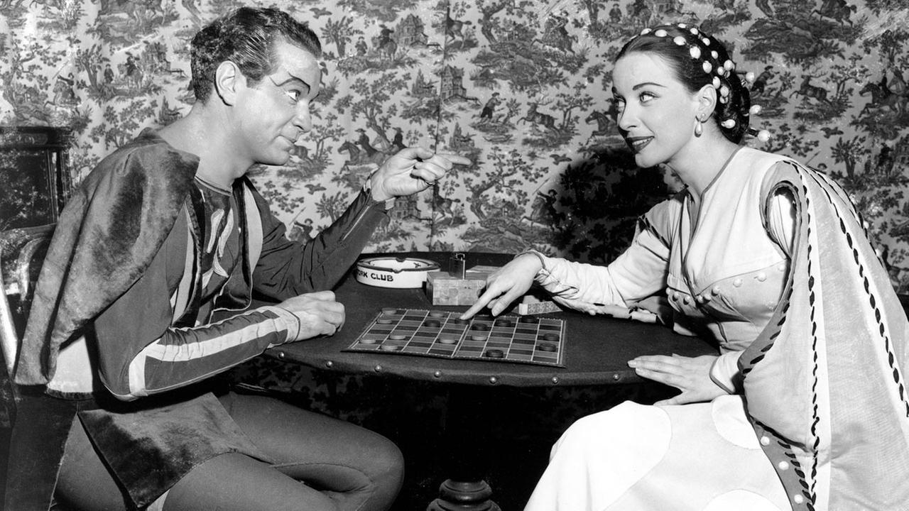 In this Dec. 25, 1949, file photo, Alfred Drake and Patricia Morison, costarring in the musical Kiss Me Kate, play checkers backstage at the New Century Theatre in New York.