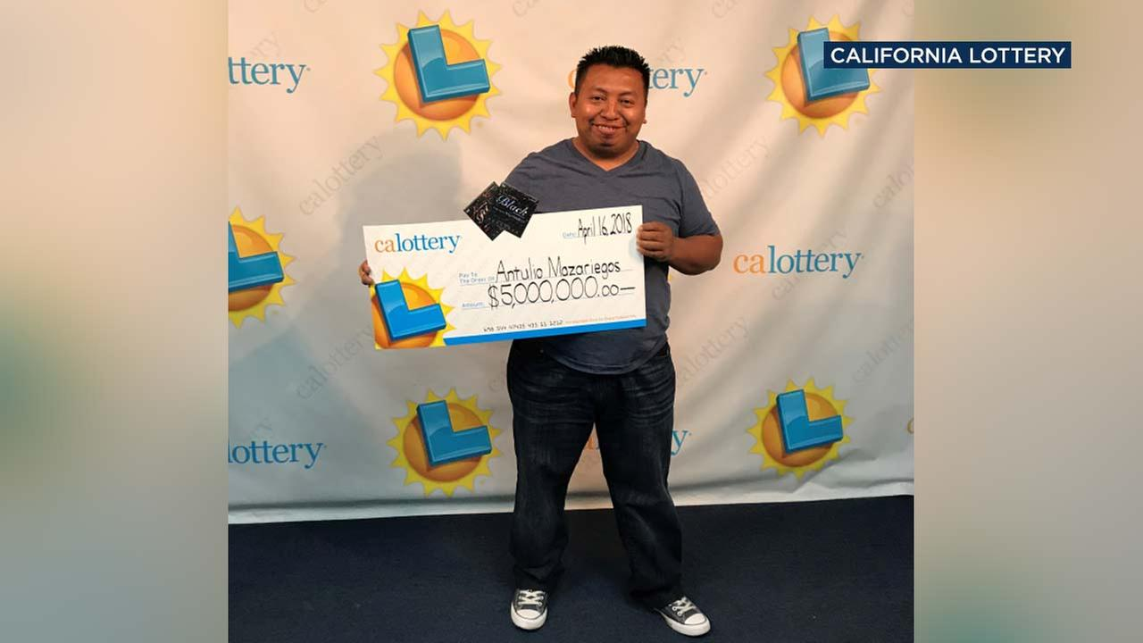 Antulio Mazariegos poses with a check for $5 million in a photo released by California Lottery officials.