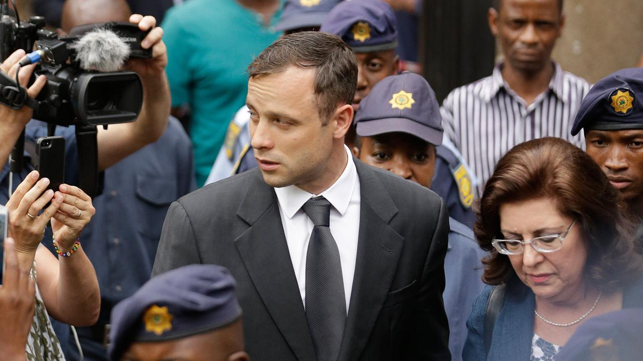 Oscar Pistorius, center, accompanied by police officers as he leaves the high court in Pretoria, South Africa, Wednesday, Oct. 15, 2014.