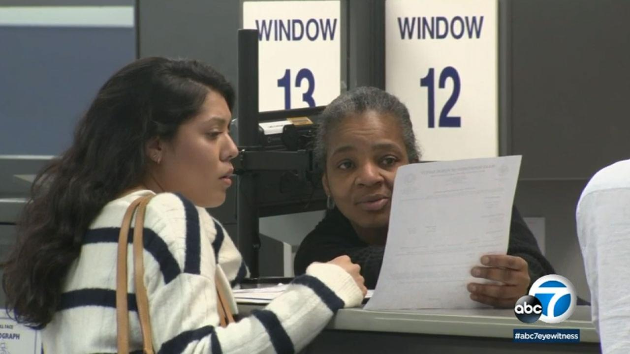 A customer hands her paperwork to a Costa Mesa DMV employee in this May 9, 2018 photo.