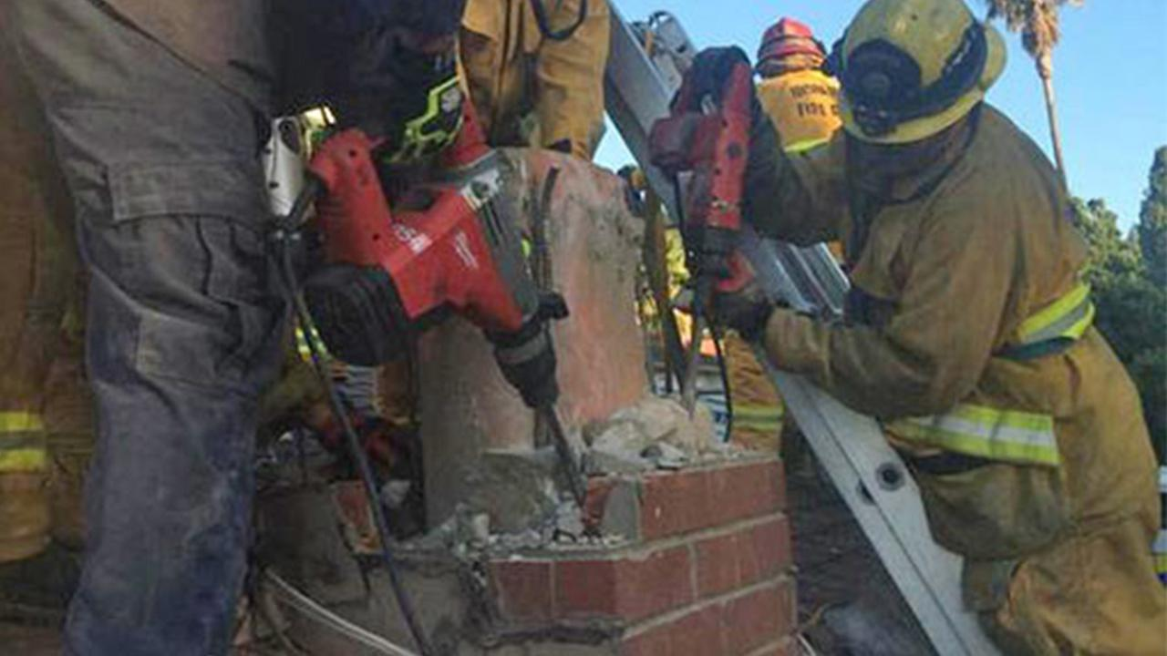 Firefighters dismantle a chimney in Thousand Oaks to save a woman trapped inside on Sunday, Oct. 19, 2014.