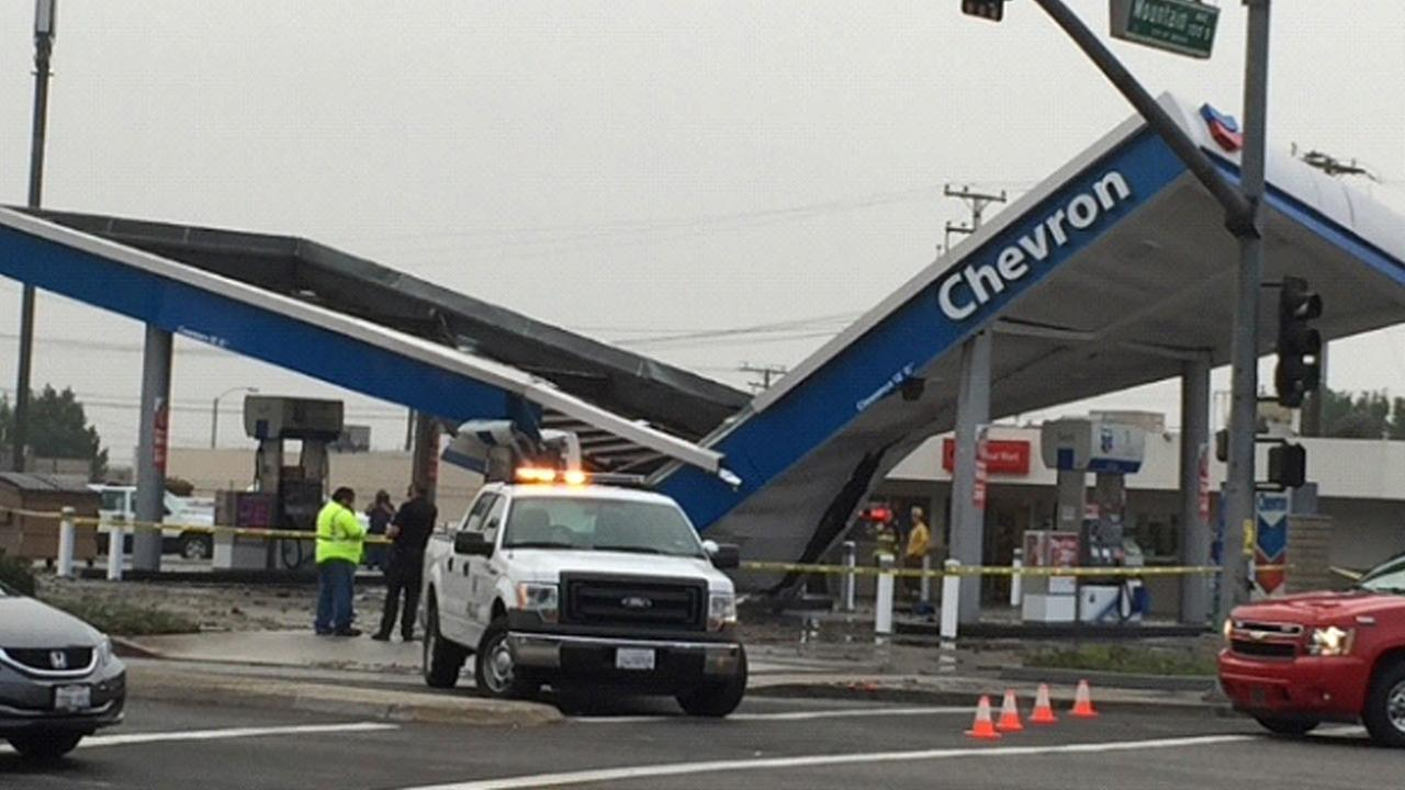 Officials inspect a collapsed roof at a Chevron gas station in Ontario on Tuesday, Oct. 21, 2014.