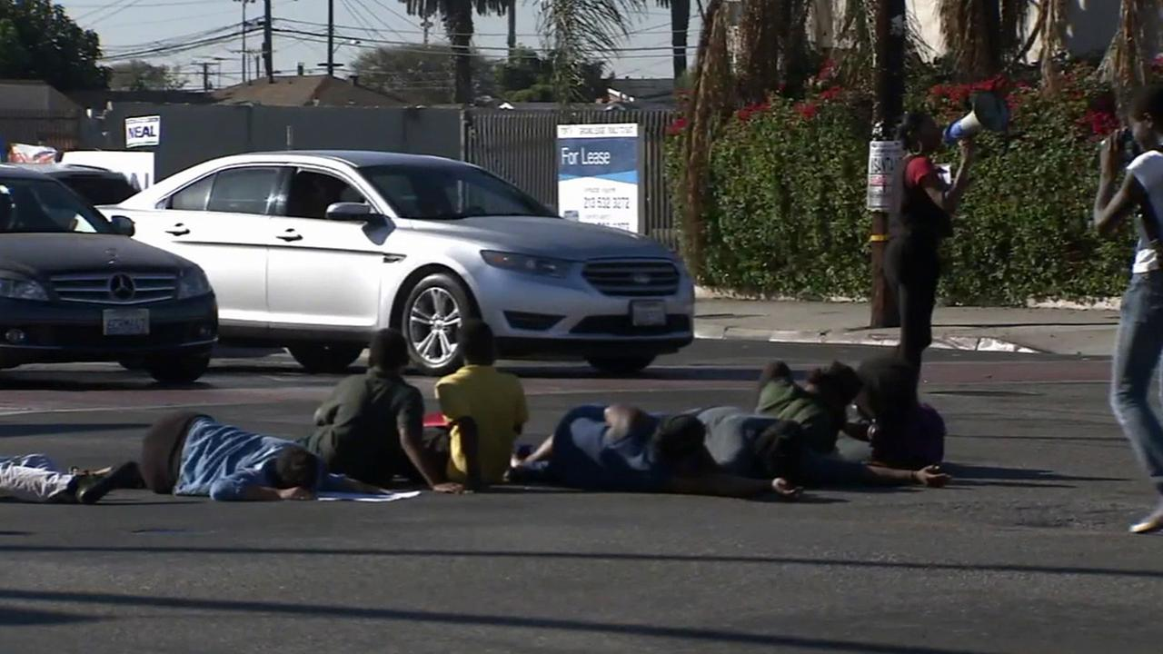 A group of protesters lie in the streets to demonstrate against the Compton Unified School Districts decision to allow officers to carry assault rifles on Friday, Oct. 24, 2014.