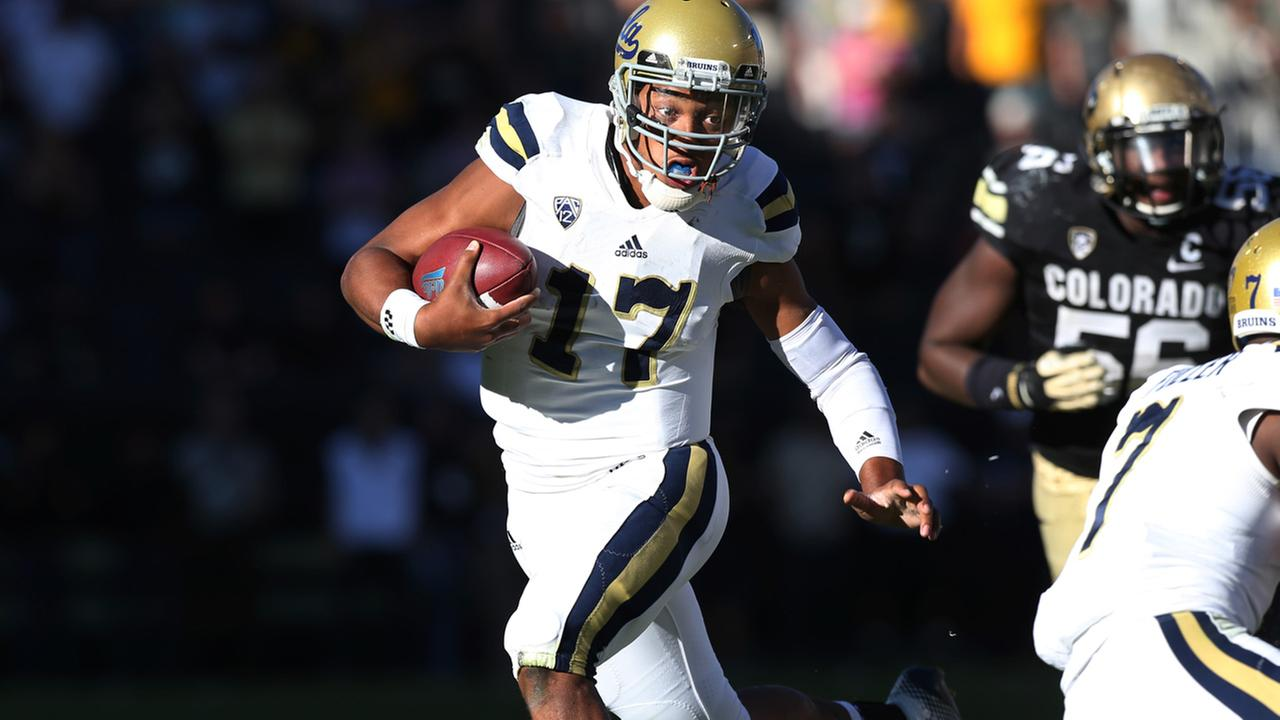 UCLA quarterback Brett Hundley, front, runs for a long gain as Colorado defensive lineman Juda parker trails in the second overtime of UCLA 40-37 victory Saturday, Oct. 25, 2014.