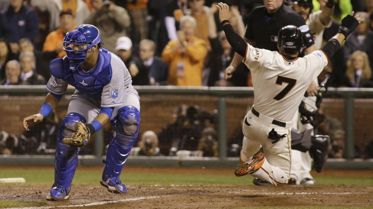 San Francisco Giants Gregor Blanco slides into home plate as Kansas City Royals Salvador Perez waits for the throw on a two-run RBI double Saturday, Oct. 25, 2014.