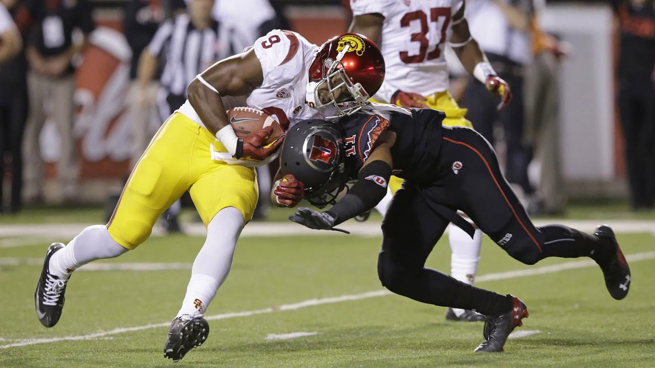 Southern California wide receiver JuJu Smith (9) takes a hit from Utah defensive back Davion Orphey (11) before scoring in the first quarter Saturday, Oct. 25, 2014.