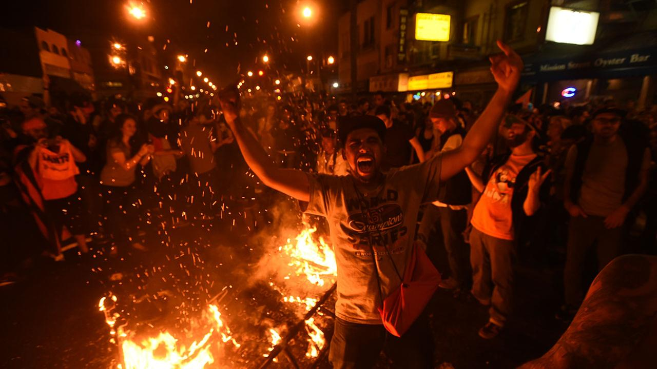 San Francisco Giants fans celebrate next to debris that has been set on fire in the Mission district after the San Francisco Giants beat the Kansas City Royals.