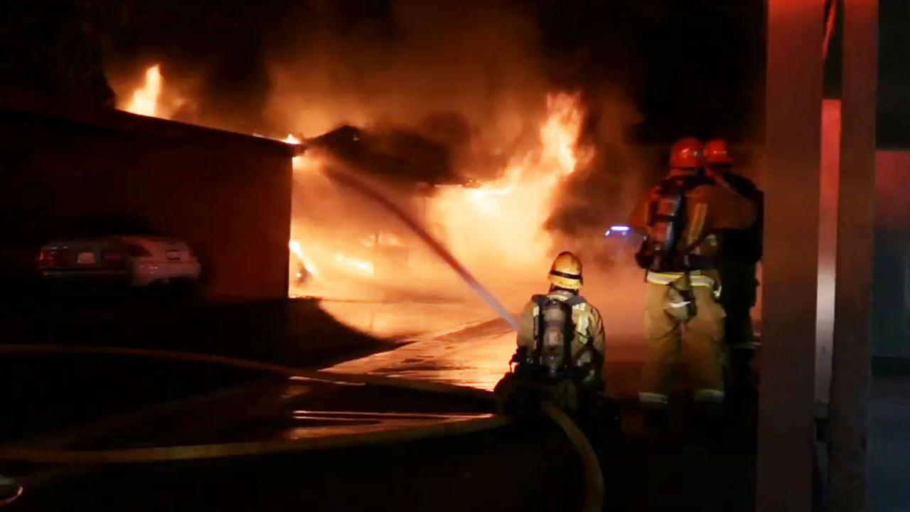 Firefighters are shown battling flames at a carport in Orange on Thursday, Oct. 30, 2014.