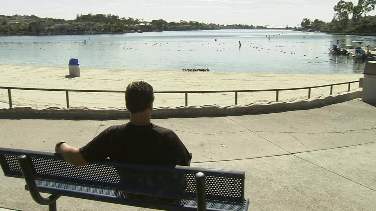 A man sits on a bench at Lake Mission Viejo in this undated file photo.