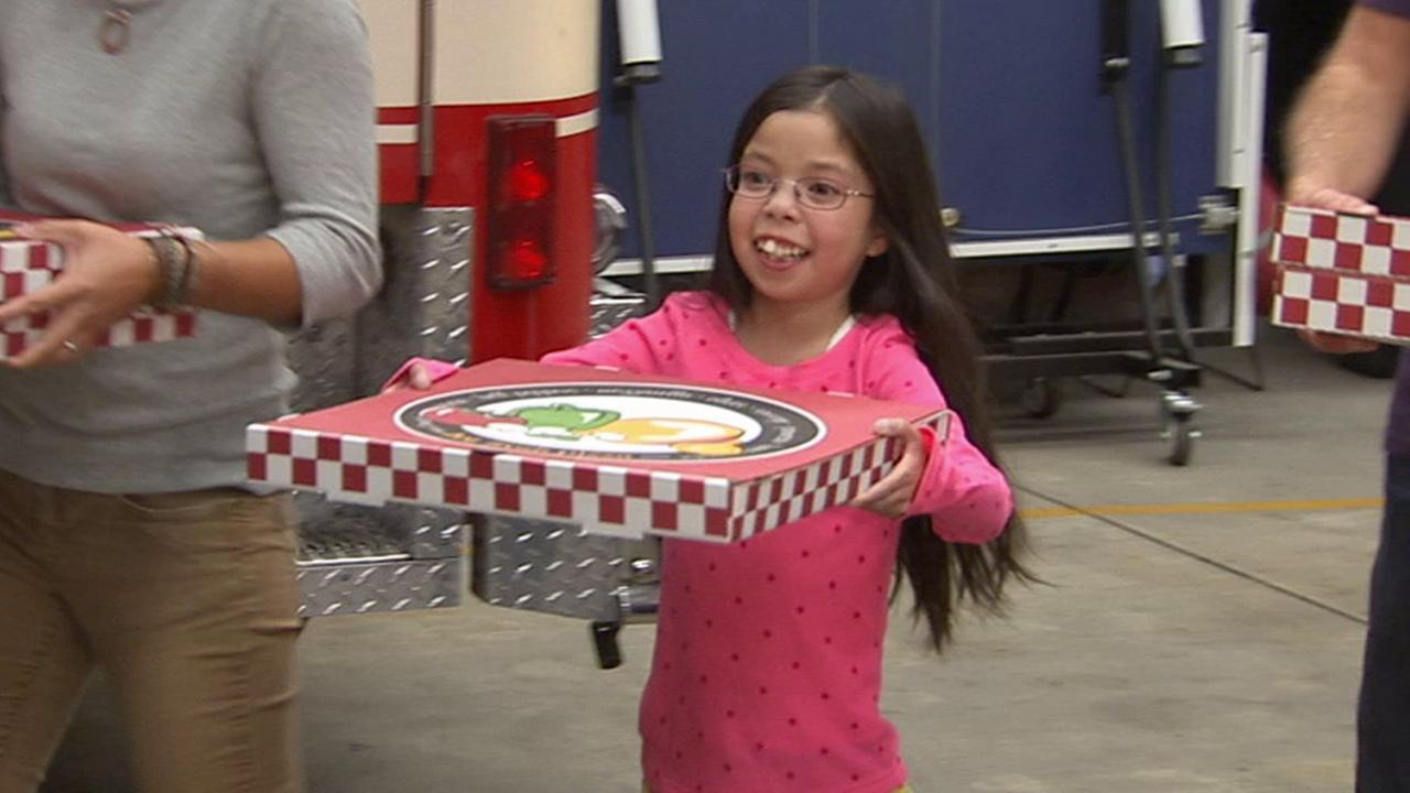 Noah Michaelis delivers pizza to firefighters at a Los Angeles Fire Department fire station in Canoga Park on Sunday, Nov. 9, 2014.