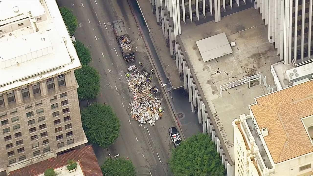 A trash truck dumped a massive pile of garbage on the streets of downtown Los Angeles after receiving reports of someone being stuck inside on Tuesday, Nov. 11, 2014.