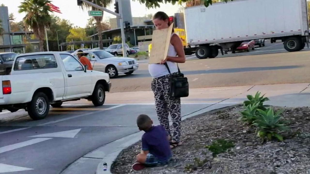 A pregnant woman panhandling with a young boy in San Diego is shown in this undated file photo.