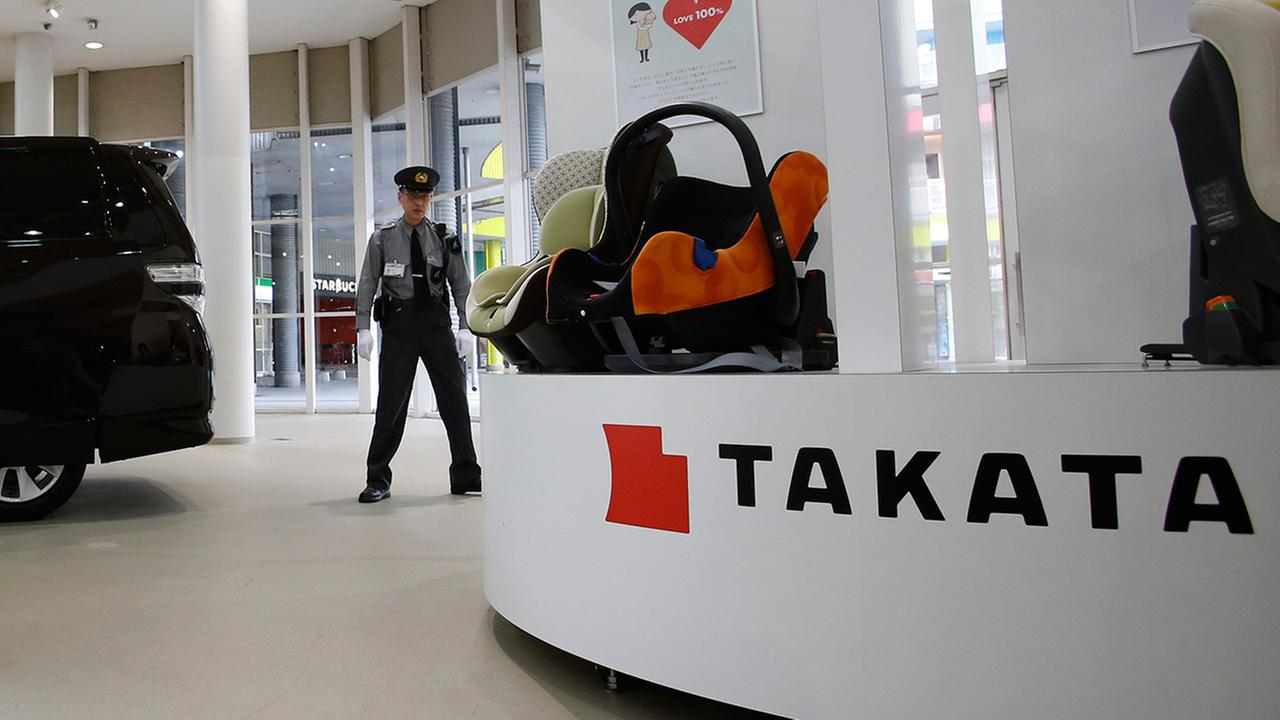 In this Nov. 6, 2014 file photo, a security guard stands by child seats, manufactured and displayed by Takata Corp. at an automakers showroom in Tokyo.