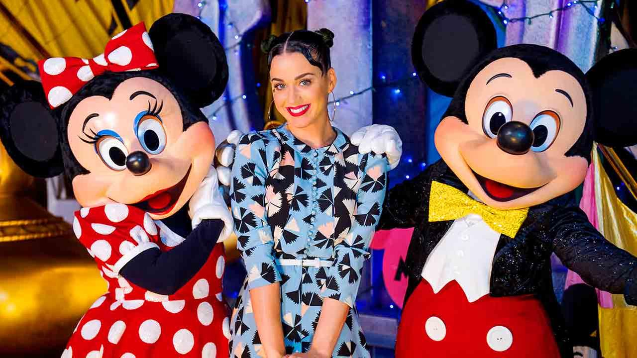 In this photo provided by Disney, singer Katy Perry, center, poses Friday, July 4, 2014, with Minnie Mouse, left, and Mickey Mouse at Disneys Hollywood Studios.