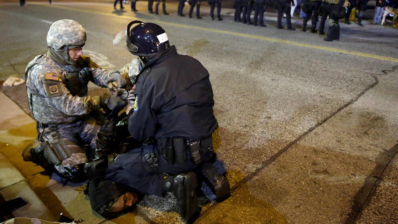 A protester is taken into custody Friday, Nov. 28, 2014, in Ferguson, Mo.