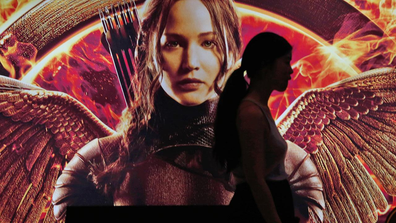 A woman is silhouetted against a billboard of the movie The Hunger Games: Mockingjay - Part 1 in Bangkok, Thailand, Thursday, Nov. 20, 2014.