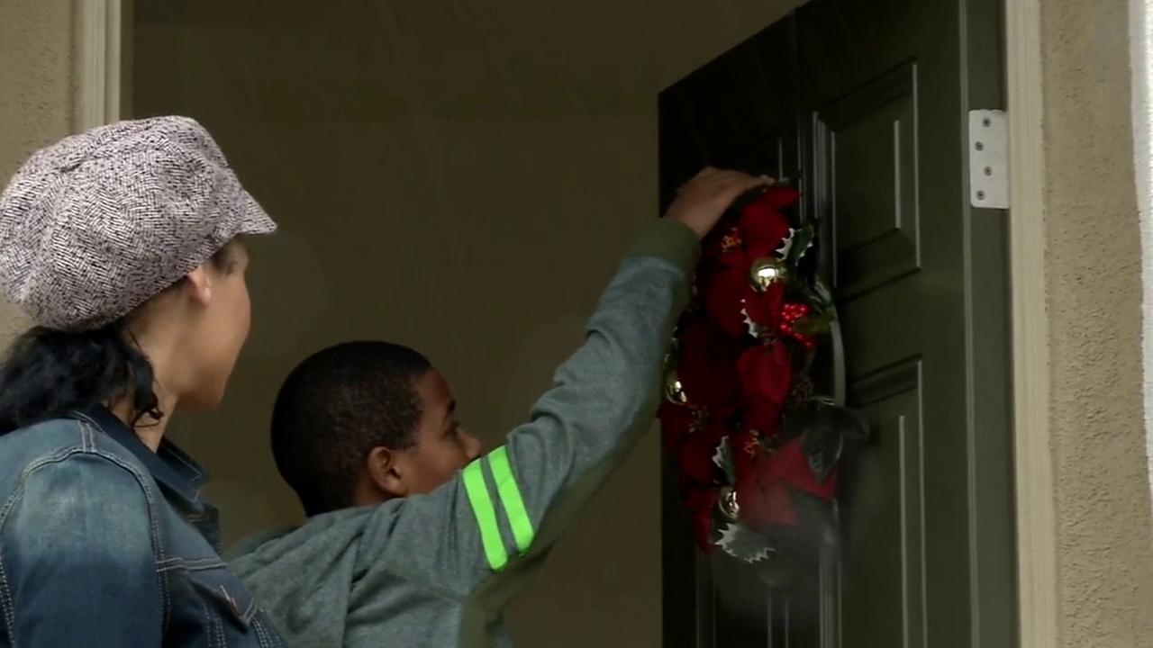 Chase Bailey, right, hangs a wreath on the front door of a Habitat for Humanity home on Tuesday, Nov. 2, 2014.