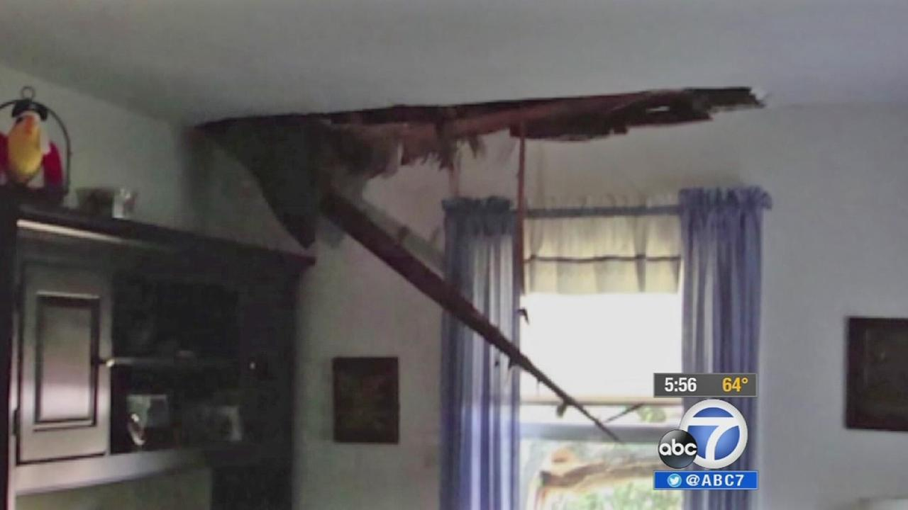 Damage is seen after a tree topples onto a home in this undated photo.