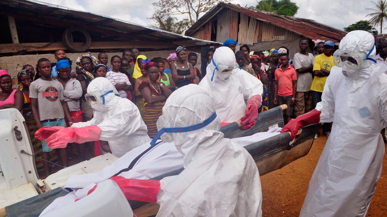 Ebola health care workers carry the body of a man suspected of dying from the Ebola virus in a small village Gbah on the outskirts of Monrovia, Liberia, Friday, Dec. 5, 2014.
