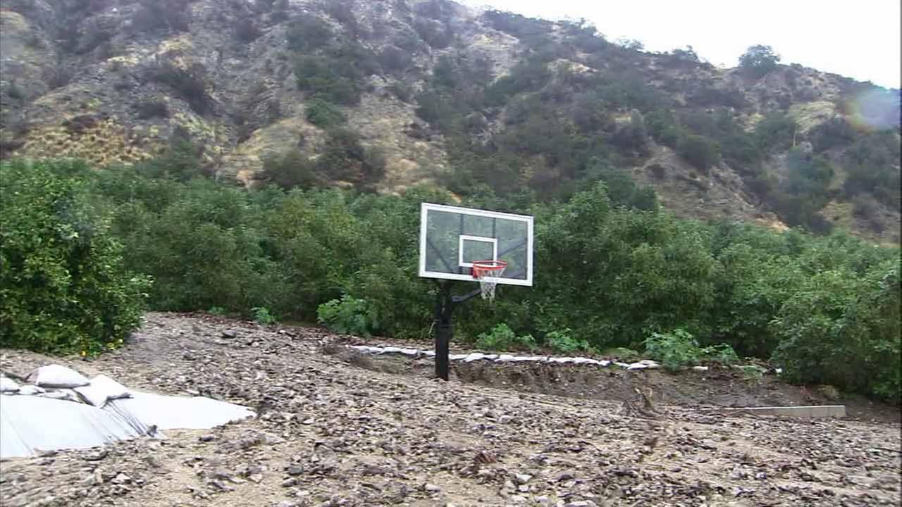 Azusa resident Ed Heinlein woke up Friday to find his basketball court completely buried in mud and debris.
