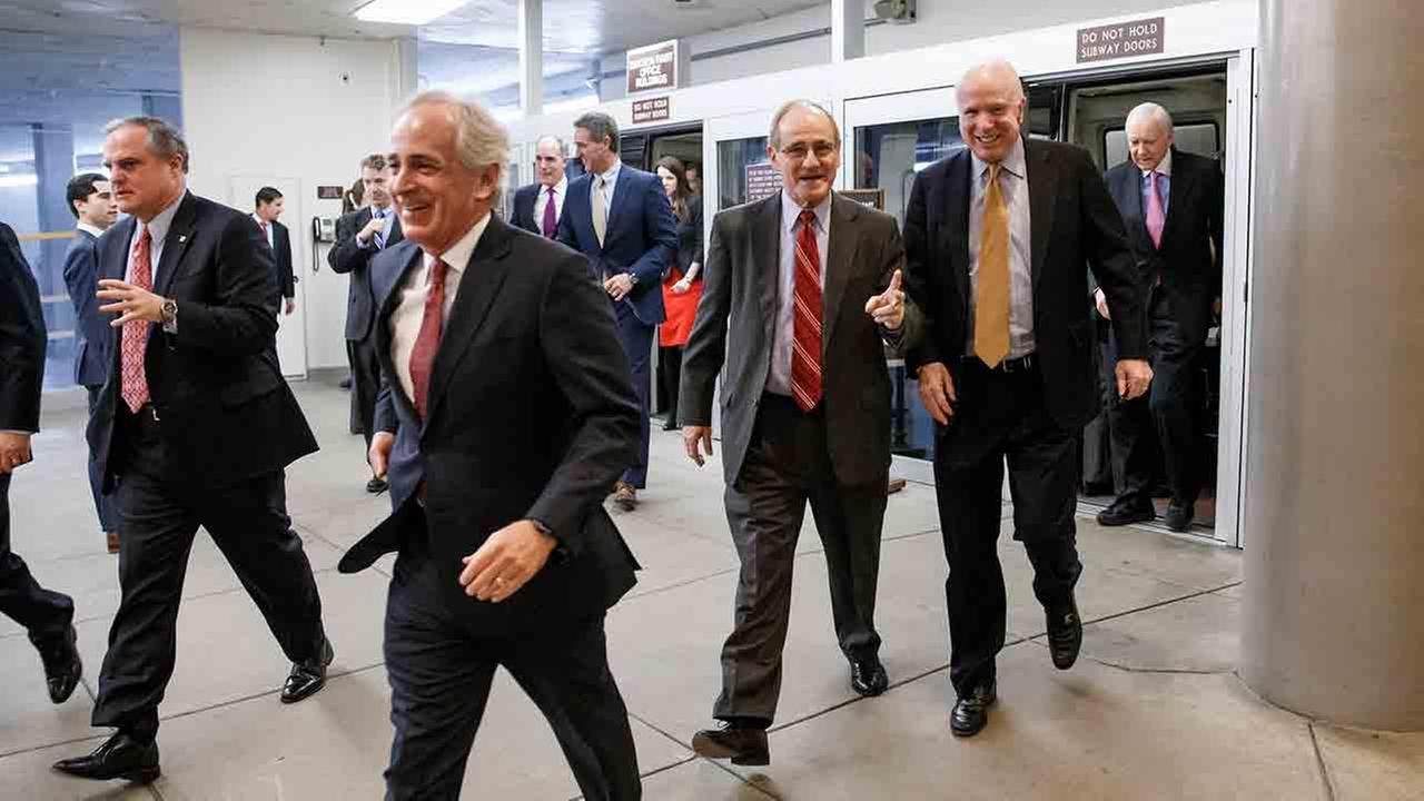 Senators rush to the Senate floor on Capitol Hill in Washington, Thursday, Dec. 11, 2014, for a procedural vote to advance the $585 billion defense bill.