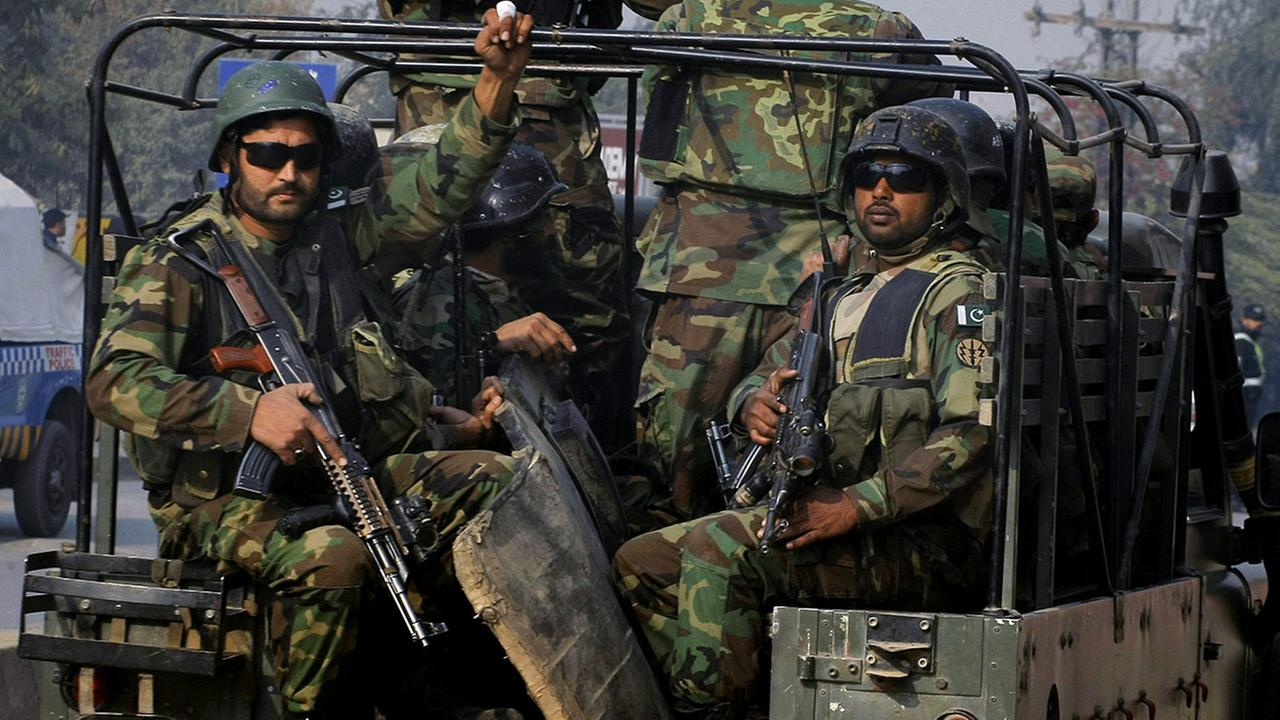 Pakistani army troops arrive to conduct an operation at a school under attack by Taliban gunmen in Peshawar, Pakistan, Tuesday, Dec. 16, 2014.