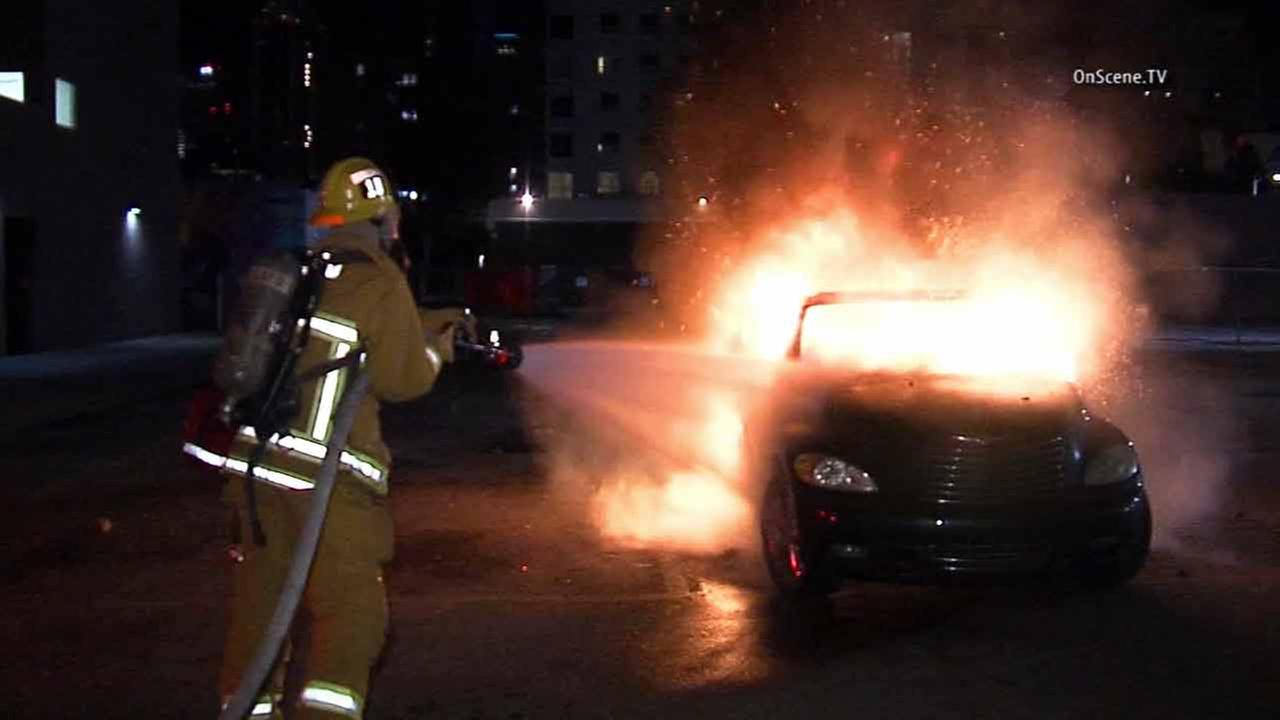 A firefighter works to put out a car fire in downtown Los Angeles on Thursday , Dec. 18, 2014.