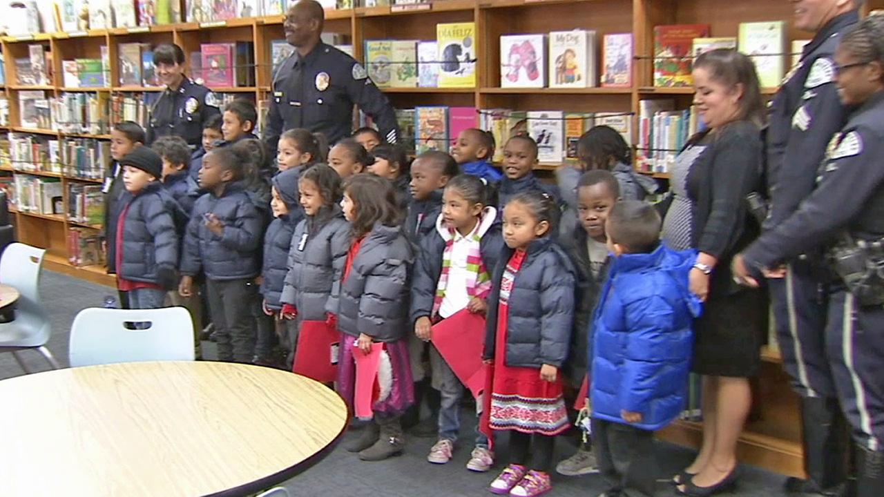 LAPD Officer Jerome Divinity (center) stands with the children he gave coats to in South Los Angeles on Thursday, Dec. 18, 2014.