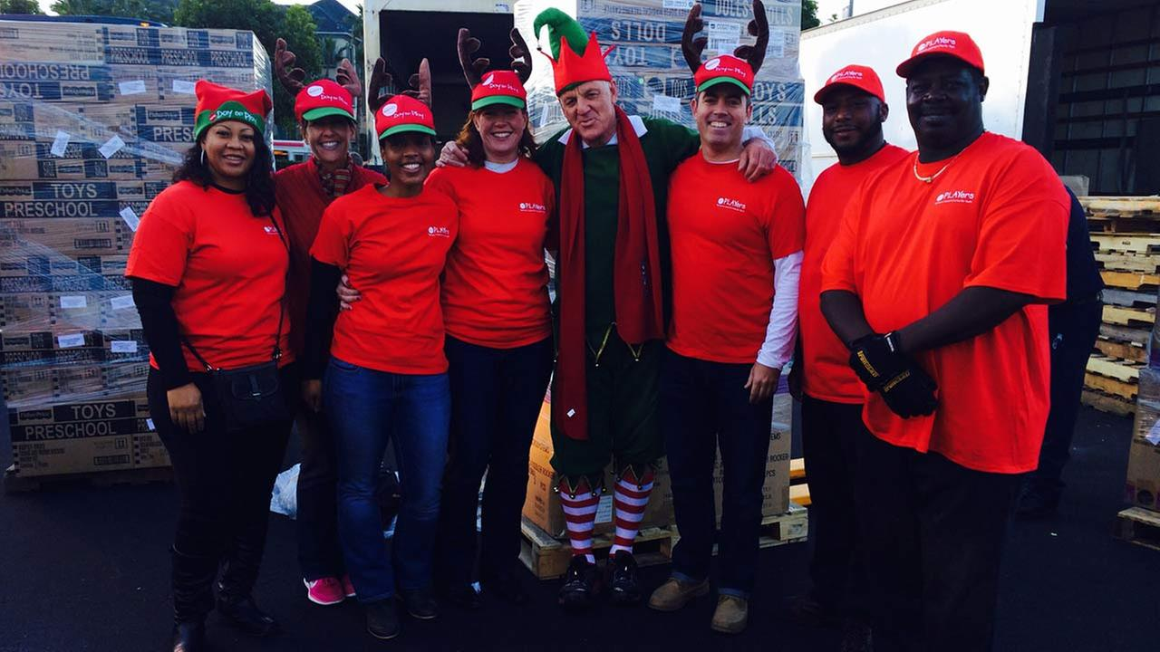 Garth Kemp poses for a photo with generous donors at the Stuff-a-Bus event in Anaheim on Friday, Dec. 19, 2014.