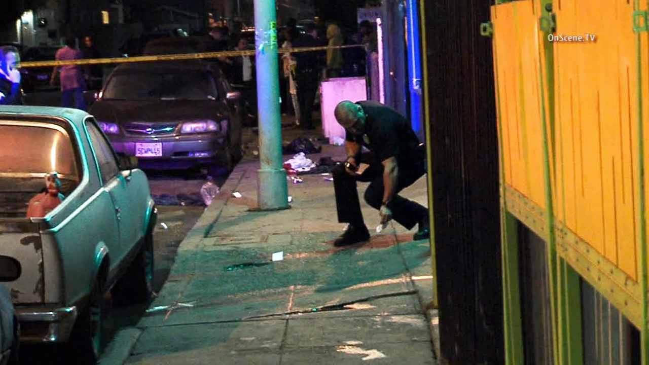 A law enforcement officer places an evidence marker at the scene of a deadly shooting near 110th Street and Wilmington Avenue in Watts on Saturday, Dec. 20, 2014.