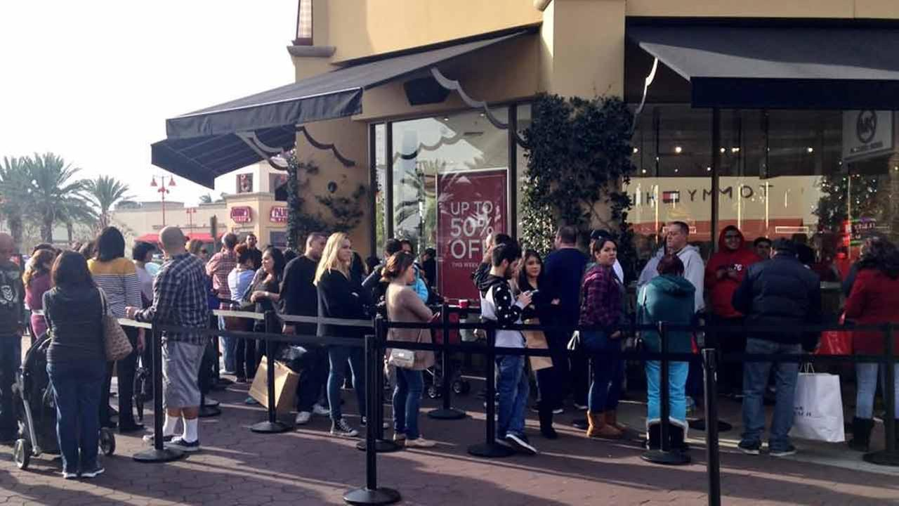 Shoppers line up outside of the Michael Kors outlet store at the Citadel Outlets in Commerce on Saturday, Dec. 20, 2014.