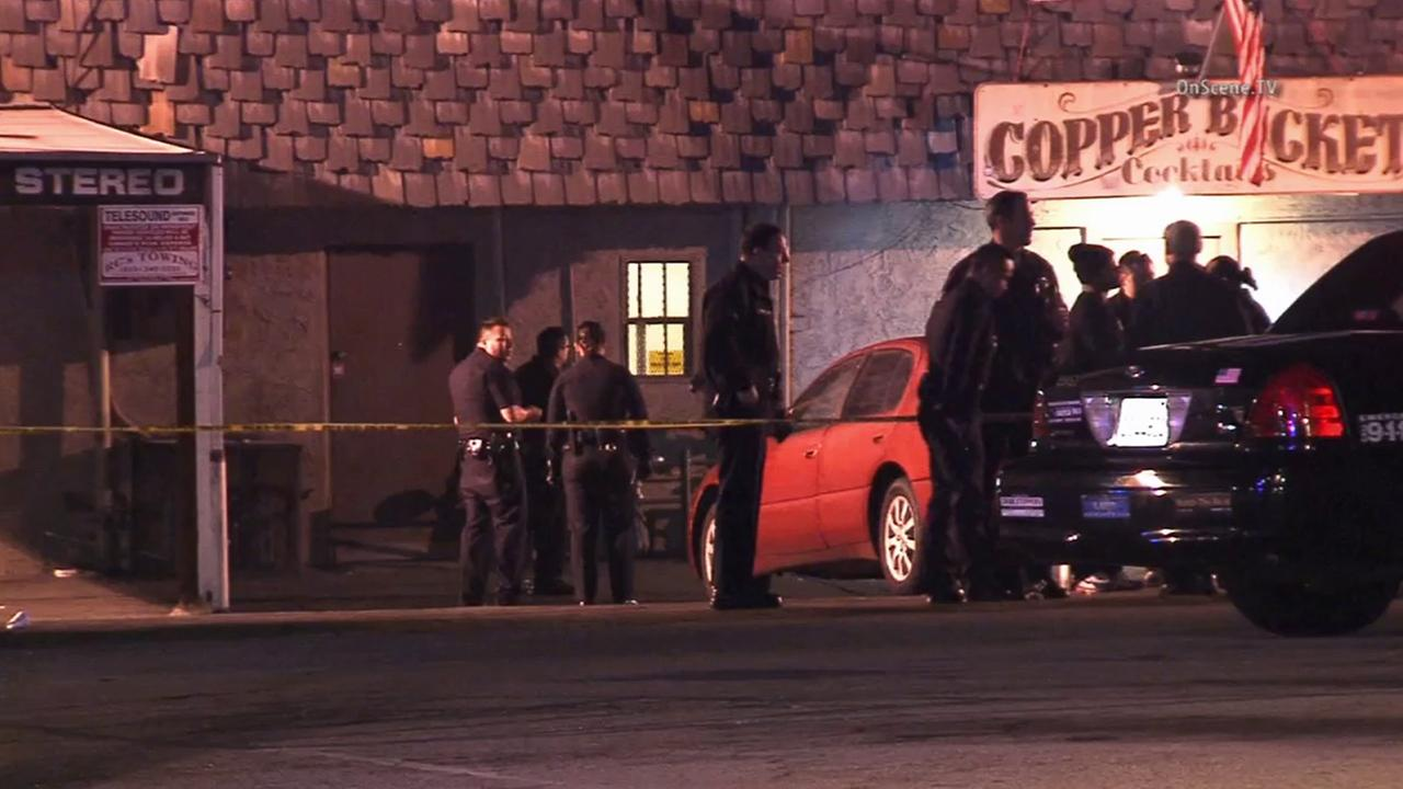 LAPD officers stand outside the Copper Bucket bar in Reseda after a shooting critically injures a man on Sunday, Dec. 21, 2014.