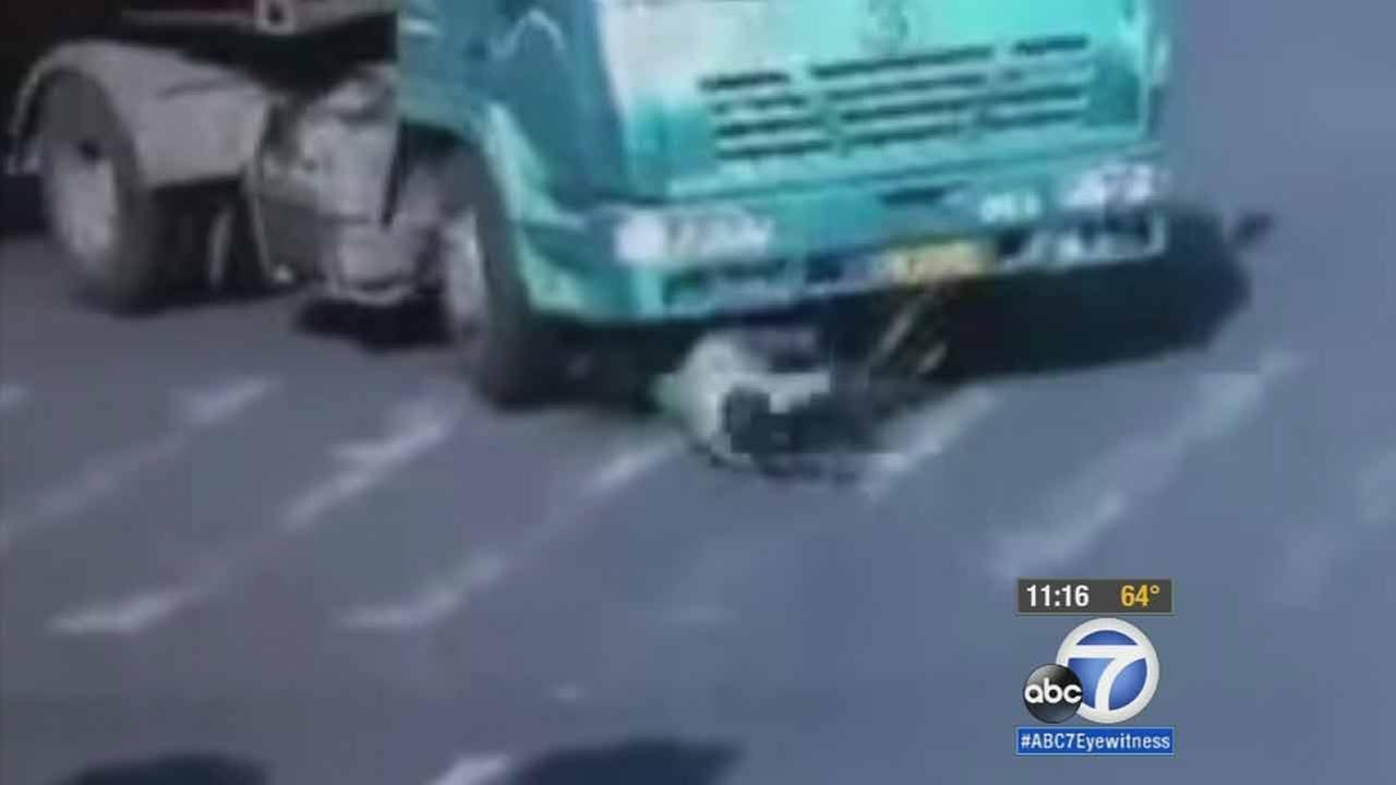 Disturbing surveillance video from China shows a cyclist getting mowed down by a cargo truck while trying to cross an intersection.