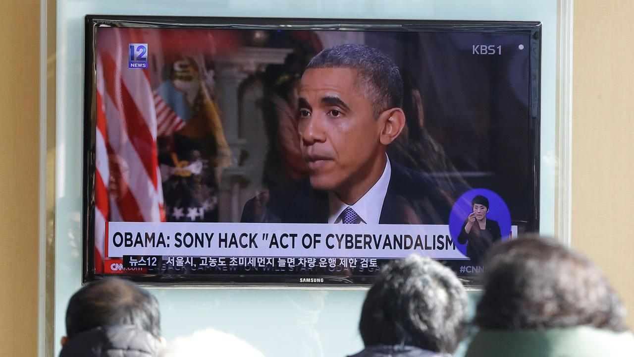 People watch a TV news program showing U.S. President Barack Obama at the Seoul Railway Station in Seoul, South Korea, Monday, Dec. 22, 2014.