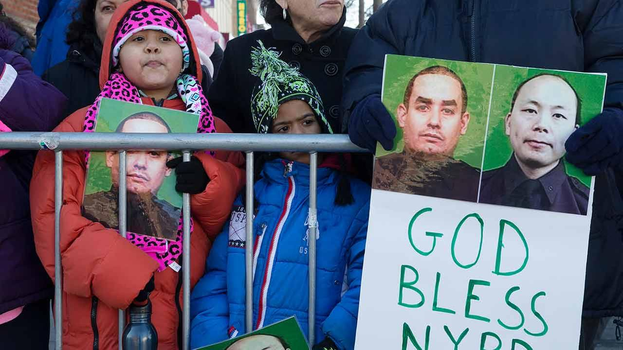 Mourners stand at a barricade near Christ Tabernacle Church in Queens as the casket of New York Police Department officer Rafael Ramos arrives for his wake Friday, Dec. 26, 2014.