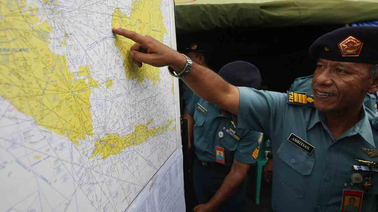 A military personnel points to a map of Indonesia at the crisis center set up by local authorities in search of the missing AirAsia flight QZ8501 at Juanda International Airport in Surabaya, East Java, Indonesia, Monday, Dec. 29, 2014.