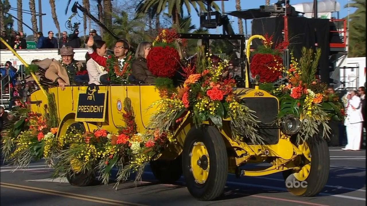 Richard L. Chinen, the president of the Tournament of Roses, waves hello while riding in a classic car.