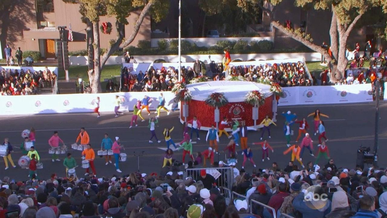 Performers jump, dance and walk past crowds watching the 2015 Rose Parade on New Years Day.