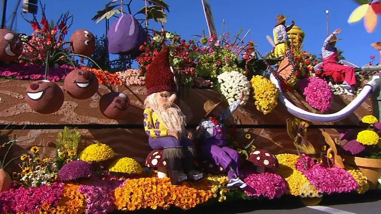 The Trader Joes float is a garden theme featuring honey bees, farmers and garden gnomes.