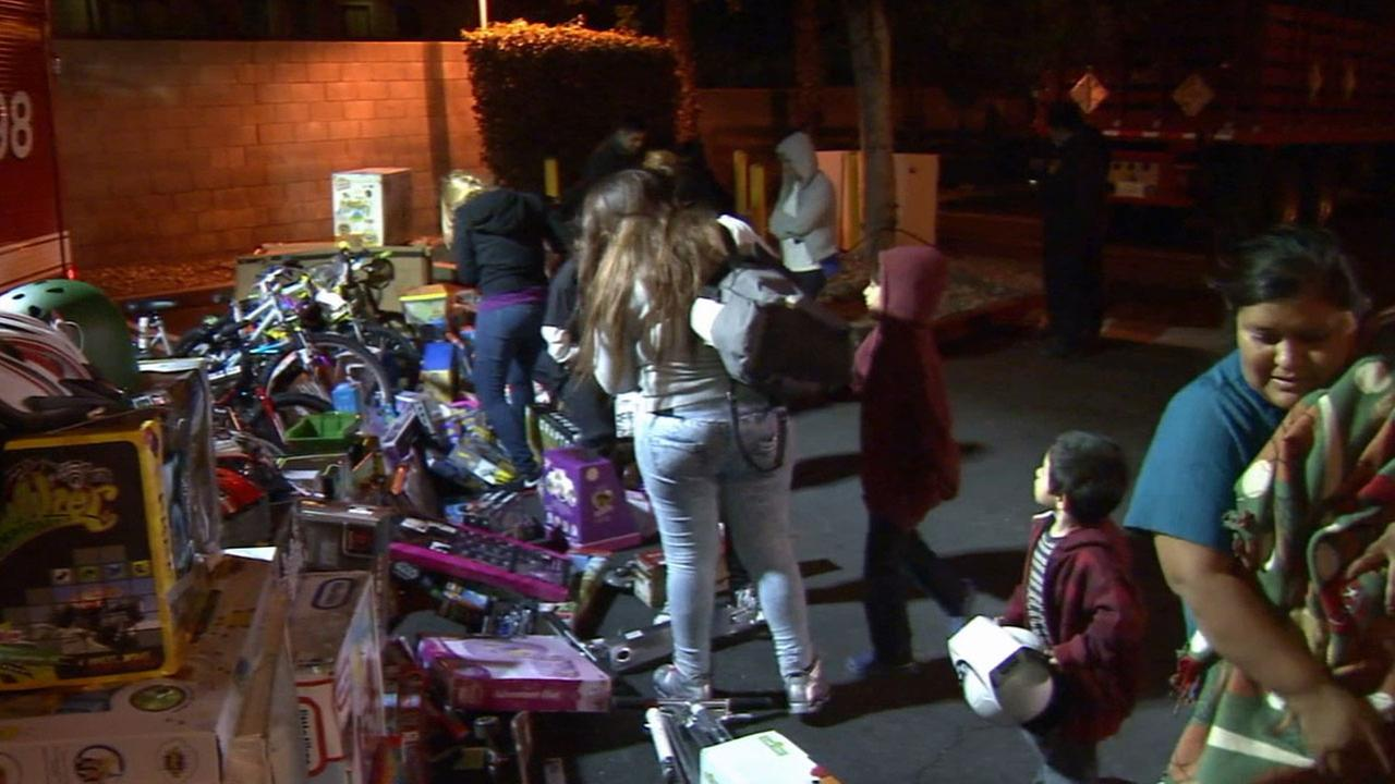Los Angeles firefighters delivered toys and gifts to a family of 21 people, including 12 children, whose Pacoima home was destroyed in a fire Saturday, Jan. 3, 2015.