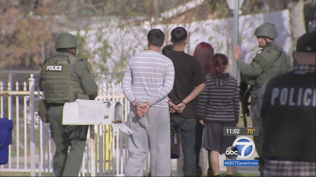 Suspects are shown being led out of a home following a standoff in San Bernardino on Thursday, Jan. 22, 2015.