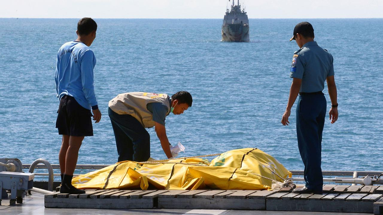 Crew members inspect bags containing bodies believed to be victims of AirAsia Flight 8501 on Indonesian Navy ship KRI Banda Aceh, on the Java Sea, Indonesia, riday, Jan. 23, 2015.