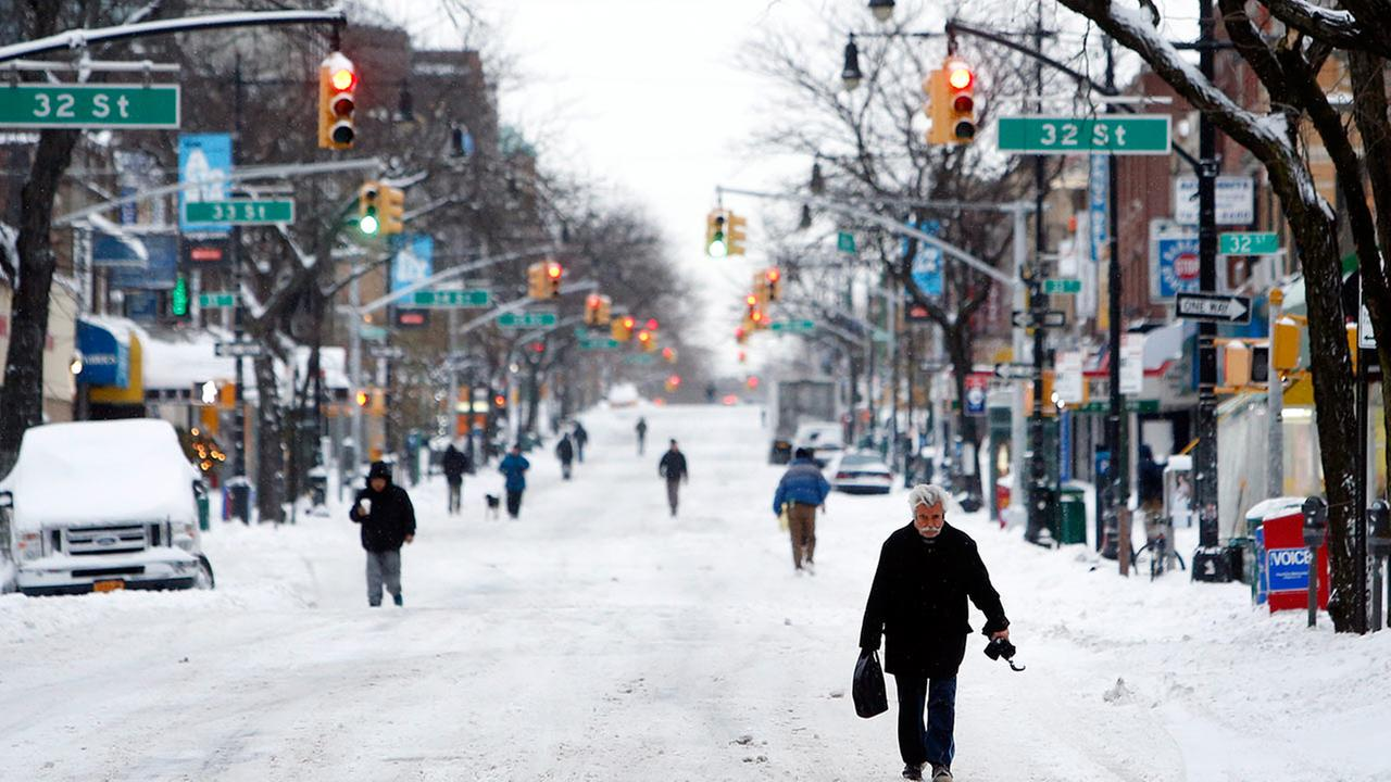 Pedestrians make their way down an empty street in the Queens borough of New York on Tuesday, Jan. 27, 2015.