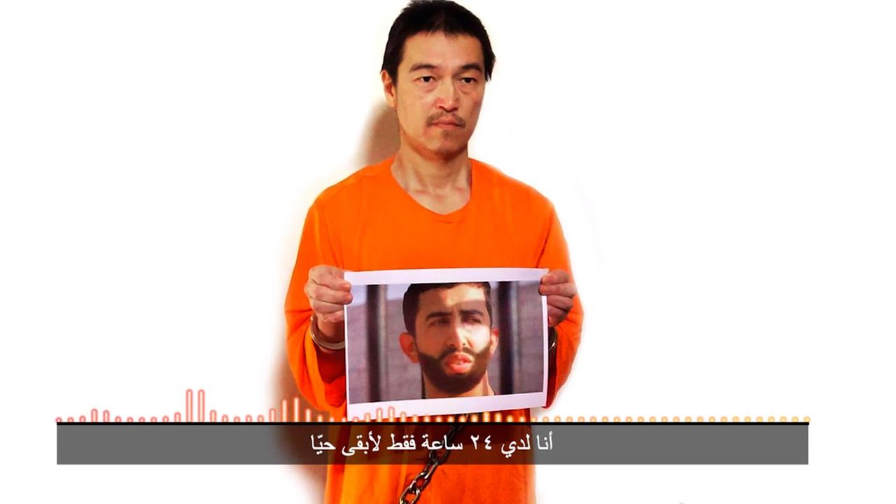 This still image taken from a video posted on YouTube by jihadists on Tuesday, Jan. 27, 2015, shows a still photo of Japanese journalist Kenji Goto holding what appears to be a photo of Jordanian pilot 1st Lt. Muath al-Kaseasbeh.