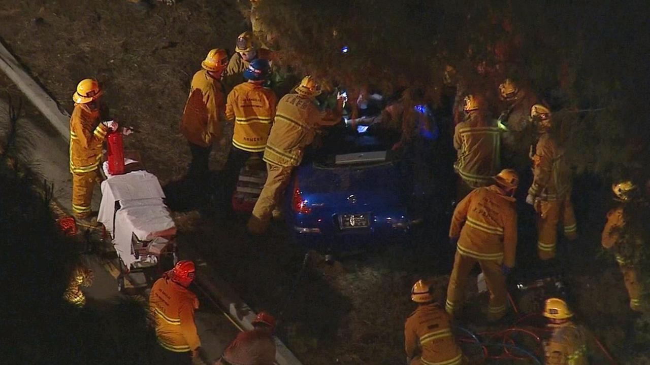 Los Angeles Fire Department firefighters work to extract a critically injured passenger from a car that crashed into a tree in Sherman Oaks on Tuesday, Jan. 27, 2015.