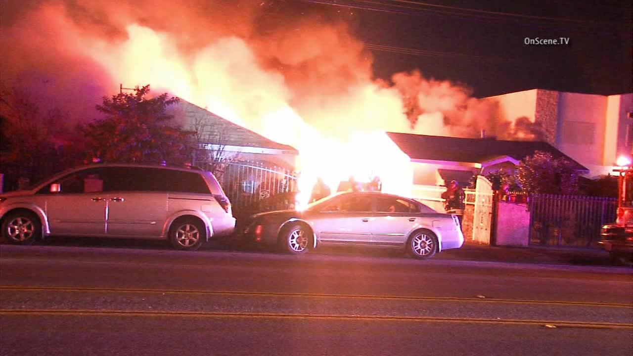 Firefighters battle flames at two homes in El Monte on Wednesday, Jan. 28, 2015.