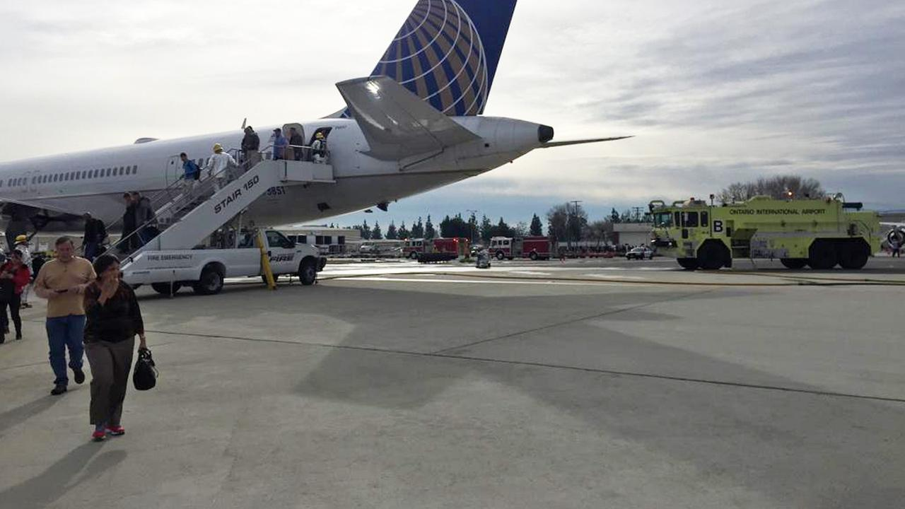 In this photo taken by passenger Mitchell Hashimoto, passengers exit United Flight 1181 after the plane made an emergency landing at Ontario International Airport.